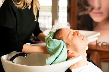 beauty parlour: Female hairdresser washing hair of smiling man client at beauty parlour