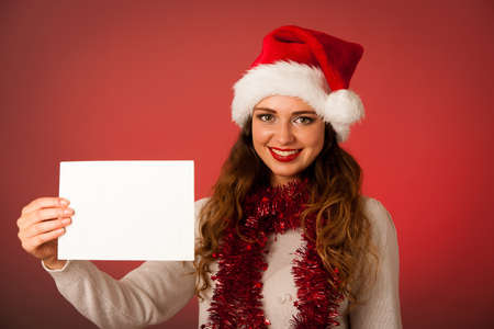 Pretty asian caucasian woman with santa claus hat celebrating christmass isolated over white background photo