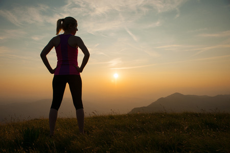 beautiful young woman runns on a mountian path at sunrise
