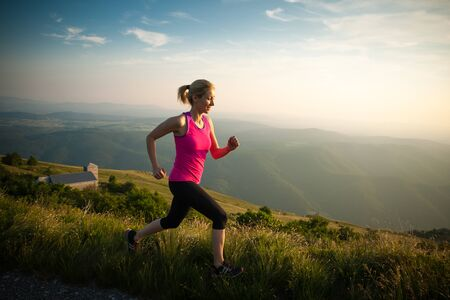 sport and leisure: beautiful young woman runns on a mountian path at sunrise