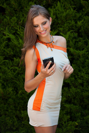 Blog style beautiful brunette woman in fashionable dress posing in park presenting garment photo