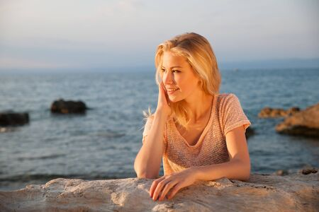 gorgeous girl: Beautiful young blonde woman resting on a beach at dusk in summer Stock Photo