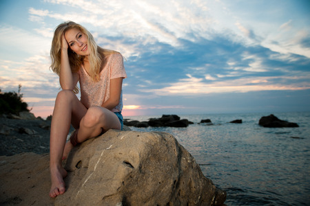 glamour girl: Beautiful young blonde woman resting on a beach at dusk in sea side
