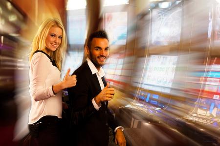 maquinas tragamonedas: pareja ganadora en la m�quina tragaperras en el casino Foto de archivo