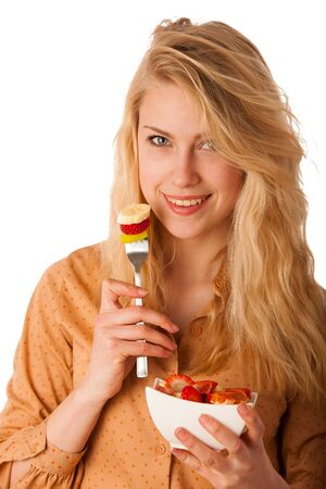 over eating: Beautiful young caucasian blonde woman holds a delicious fruit salad as a sign for healthy eating isolated over white background Stock Photo