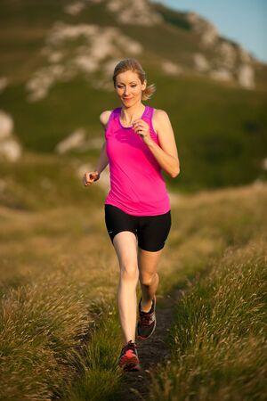 beautiful young woman runs on a mountain path at sunrise