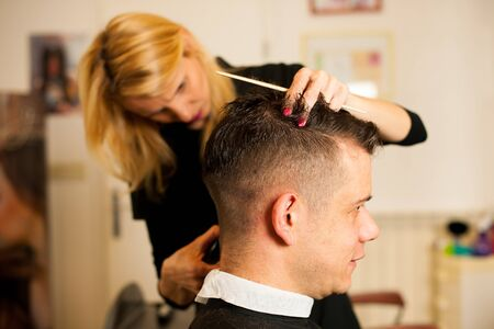 beauty women: Female hairdresser cutting hair of smiling man client at beauty parlour
