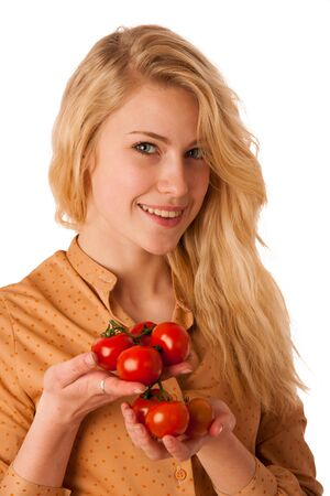 blue eyes: Beautiful young blond caucasian cheerful woman with blue eyes holds red cherry tomatoes isolated over white