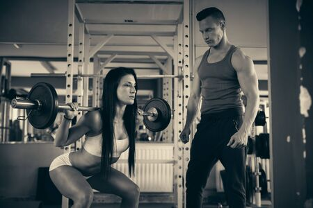 personal: Personal fitness coach trains a beautiful woman in gym