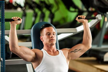 powerful man: physique fitness competitor works out in gym Stock Photo