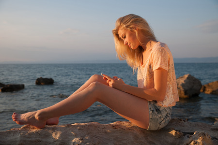 gorgeous girl: Beautiful young blonde woman resting on a beach at dusk in summer - sea side sunset Stock Photo