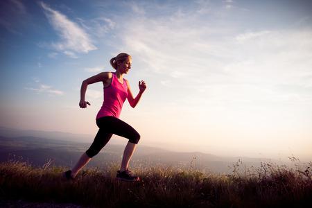 schöne junge Frau auf einem runns mountian Weg bei Sonnenaufgang Lizenzfreie Bilder