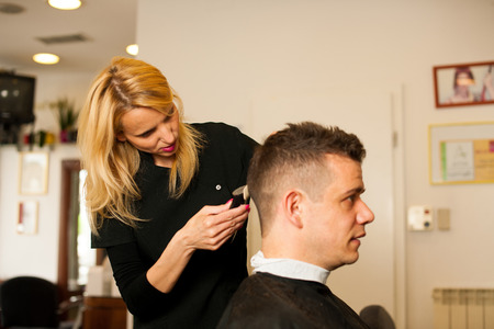 cut: Female hairdresser cutting hair of smiling man client at beauty parlour