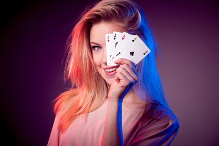Mujer caucásica hermosa con las tarjetas del póker que juegan en casino Foto de archivo