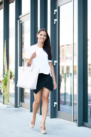hand bag: Young attractive happy woman outdoors walking on a street with hand bag in her hand