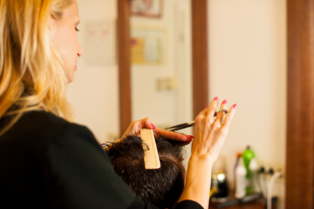 beauty parlour: Female hairdresser cutting hair of smiling man client at beauty parlour