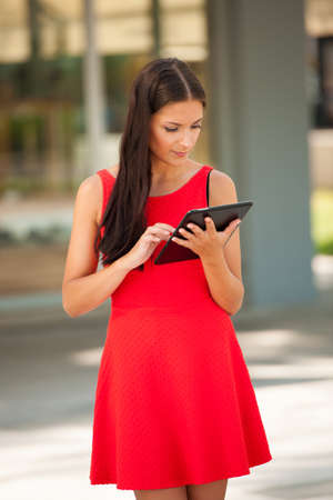 surfing the web: Beautiful young business woman surfing web on a tablet outdoor in the city