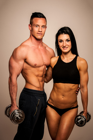 athletic body: Fitness couple poses in studio - fit man and woman