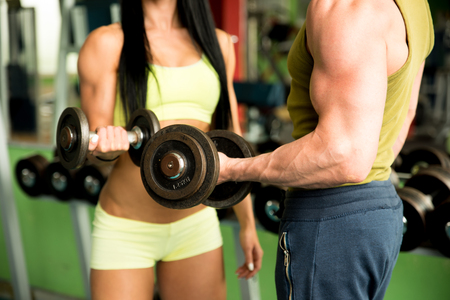 dumbbell: Fitness couple working out in gym with dumbbells