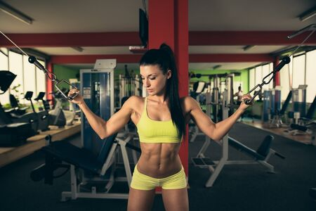 intervals: Beautiful fit woman working out in gym - girl in fitness