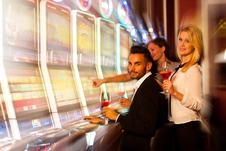 tragamonedas: jóvenes jugando máquinas tragamonedas en el casino