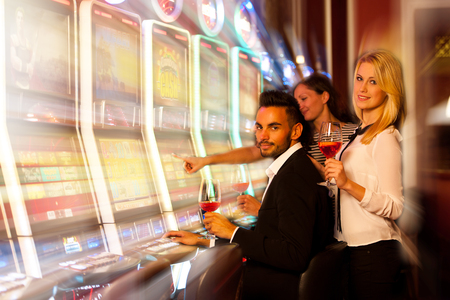man machine: young people playing slot machines in casino