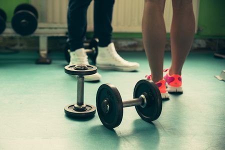 flor: Dumbbell on a flor in fitness gym with legs in background