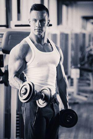 cuerpo hombre: competidora de fitness phisique trabaja en el gimnasio levantando pesas