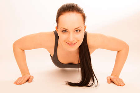 ups: woman doing push ups in fitness Stock Photo