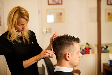 male  beauty: Female hairdresser cutting hair of smiling man client at beauty parlour