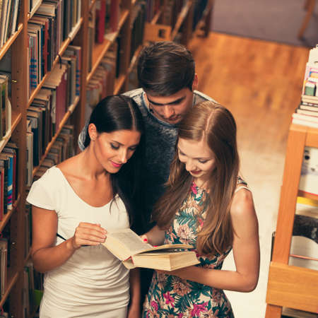 study group: Group of students in library reading books - study group Stock Photo