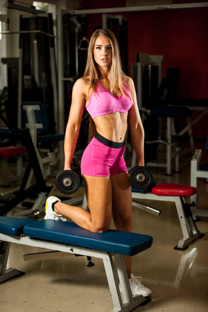 girl working out: Fitness workout - Popular beautiful young woman workout in fitness gym, training body building for bikini fitness category competition Stock Photo