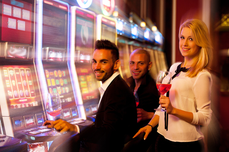 machines: young people playing slot machines in casino