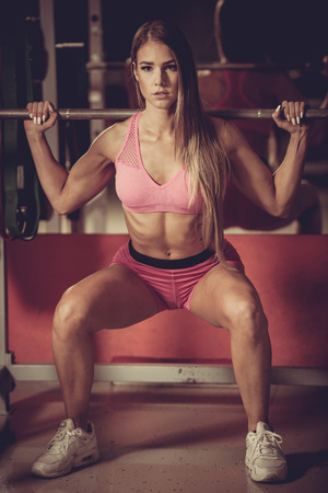 sweat girl: Fitness workout - Popular beautiful young woman workout in fitness gym, training body building for bikini fitness category competition Stock Photo