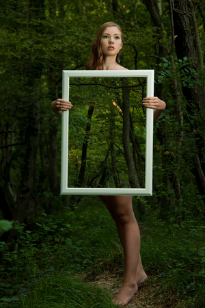 Lady nature - beoutiful young wman stands in nature with a frame that makes her transparent and stresses on beauty of background