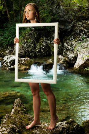 naked woman: Леди природа - beoutiful молодой WMAN стоит в природе с рамой, что делает ее прозрачной и подчеркивает красоту на фоне Фото со стока