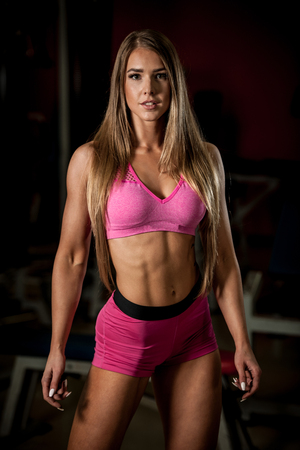 female sexy chains: Fitness workout - Popular beautiful young woman workout in fitness gym, training body building for bikini fitness category competition Stock Photo