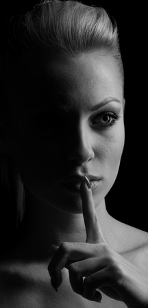 mystery woman: Mystery woman in shadow with finger on lips gesturing silence. Dark portrait. Stock Photo