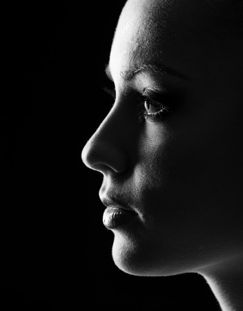face close up: Portrait of beautiful blonde woman in darkness with soft light on her face, pensive silhuette in on black background.