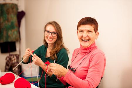Frauen mit roter Wolle stricken. Senioren Frau, die ihre Kenntnisse über Stricken auf eine jüngere Frau, die auf Handwerk Werkstatt Übertragung.