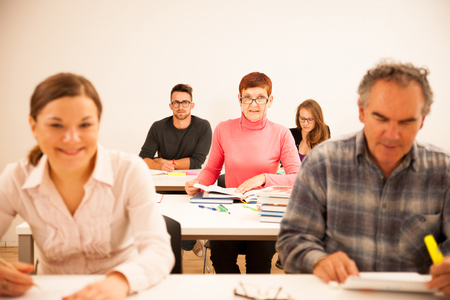 Group of people of different age sitting in classroom and attending a school for adults. Lifelong learning. Archivio Fotografico