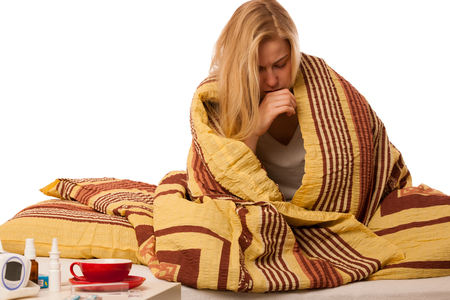 cold: Sick woman sitting on bad wrapped in a blanket feeling ill, has flu, fever, cold and cough.