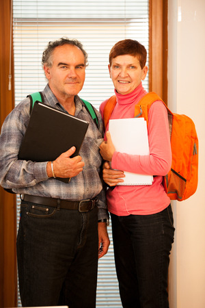 lifelong: Older couple representing lifelong learning. Couple with school bags smiling as a gesture of happiness and joy of learning. Stock Photo
