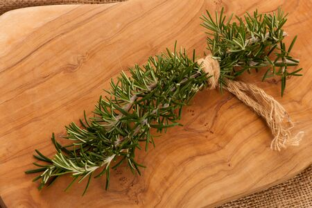 mediterranian: Twigs of green fresh rosemary, mediterranian spice, tied in bouquet, on wooden background.