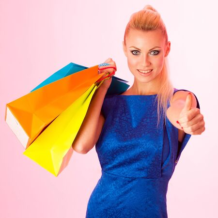 bought: Happy blonde woman holding bunch of vibrant shopping bags after she bought a lot of things on sale in different shops.