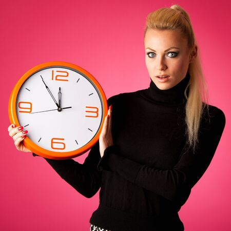 delay: Worried woman with big orange clock gesturing delay, rush, nervous, stress because of lack of time.