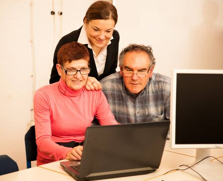 Young woman teaching elderly couple of computer skills. Intergenerational transfer of knowledge. Stock Photo