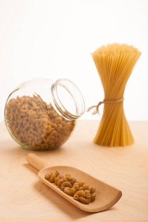 tied in: Wheat spaghetti standing tied in bundle and glass jar filled with spelt pasta in the shape of fusilli. Stock Photo