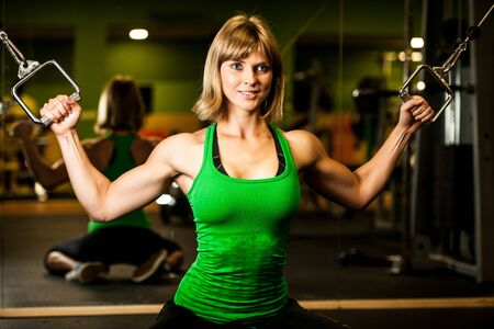 sweat girl: beautiful muscular fit woman exercising building muscles in fitness gym