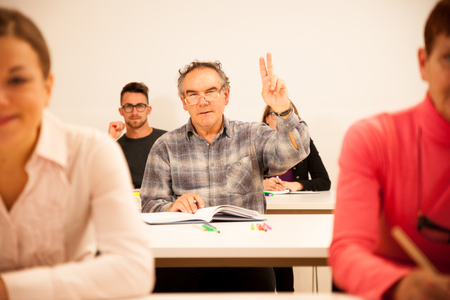 Group of people of different age sitting in classroom and attending a school for adults. Lifelong learning. Stock Photo
